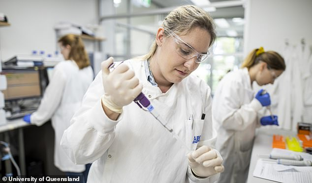 The vaccine under development uses groundbreaking 'molecule clamp' technology which fuses together a synthetic COVID-19 spike protein (pictured, the researchers at work)