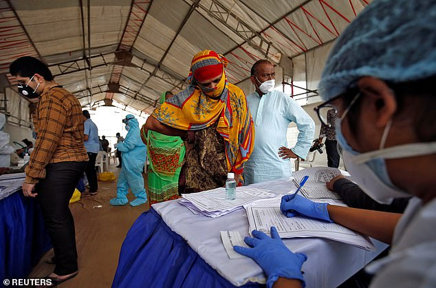 People get their details recorded before giving their swabs for rapid antigen tests, amid the coronavirus outbreak, at a check-up point in Ahmedabad, India