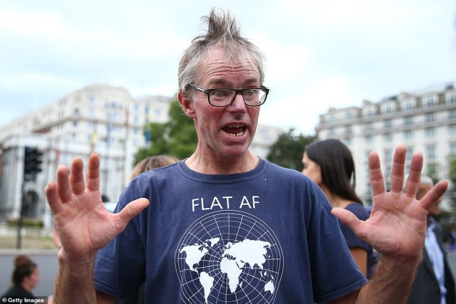 A man wearing a flat earth shirt described the conspiracy theory to a fellow demonstrator at the Keep Britain Free march