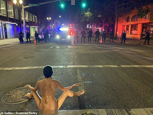 A protester dubbed 'Naked Athena' confronted Portland police wearing only a face mask and beanie