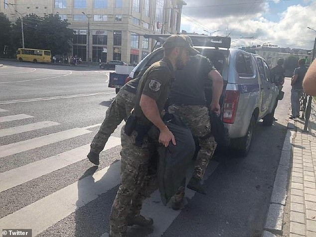 Police collect supplies as they walk to the bus where 20 people were taken hostage by a gunman