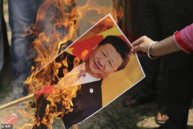 Activists in India are pictured burning a photograph of Chinese President Xi Jinping following a June border stoush that claimed the lives of 20 Indian soldiers