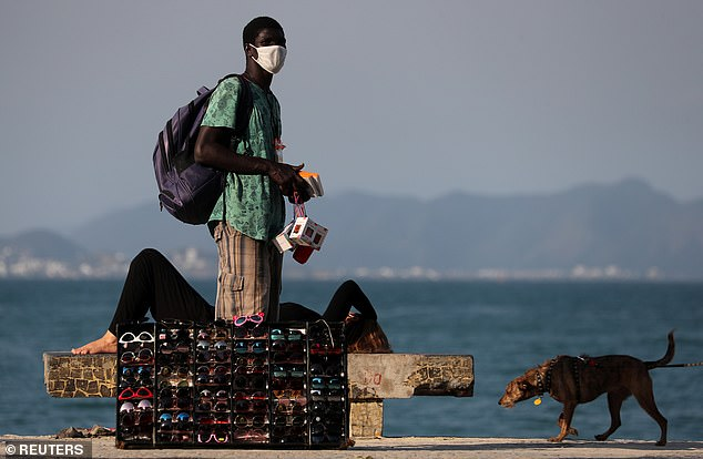 A sunglasses vendor is seen on Copacabana Beach, amid the coronavirus (COVID-19) outbreak, in Rio de Janeiro, Brazil, last week