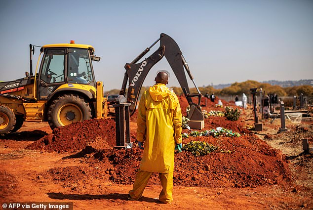 SOUTH AFRICA: A funeral director wearing personal protective equipment watches an excavator fill a grave during the funeral of a coronavirus victim in Johannesburg yesterday