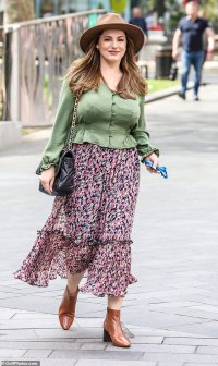 Kelly Brook goes for rustic chic in a fedora hat, green silk blouse and flowing floral skirt
