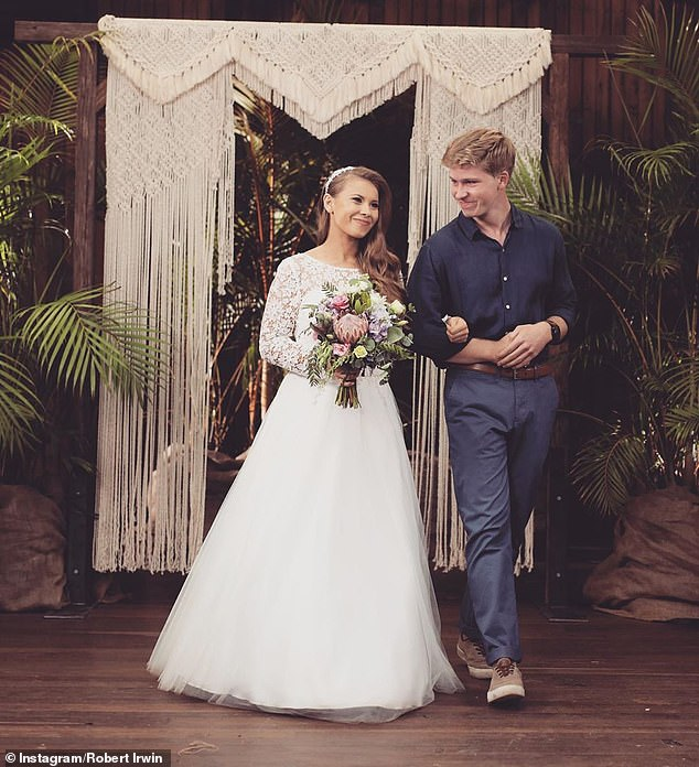 'Beyond blessed to be your sister': The birthday girl was quick to reply back, saying: 'Love you so much, Brian! Thank you for being the greatest friend and brother.' Robert pictured walking with Bindi on her wedding day