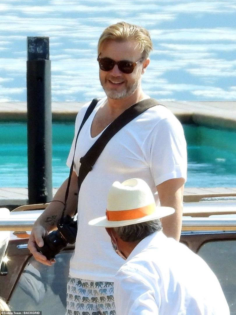 Dapper: Gary wore a simple white shirt over his swimming trunks as they headed back to town