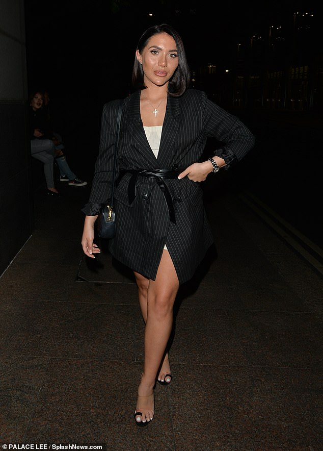 Chic:Chloe meanwhile cut a glamorous figure in an oversized black pinstripe blazer which she wore as a dress, with the look pulled together with a black leather belt