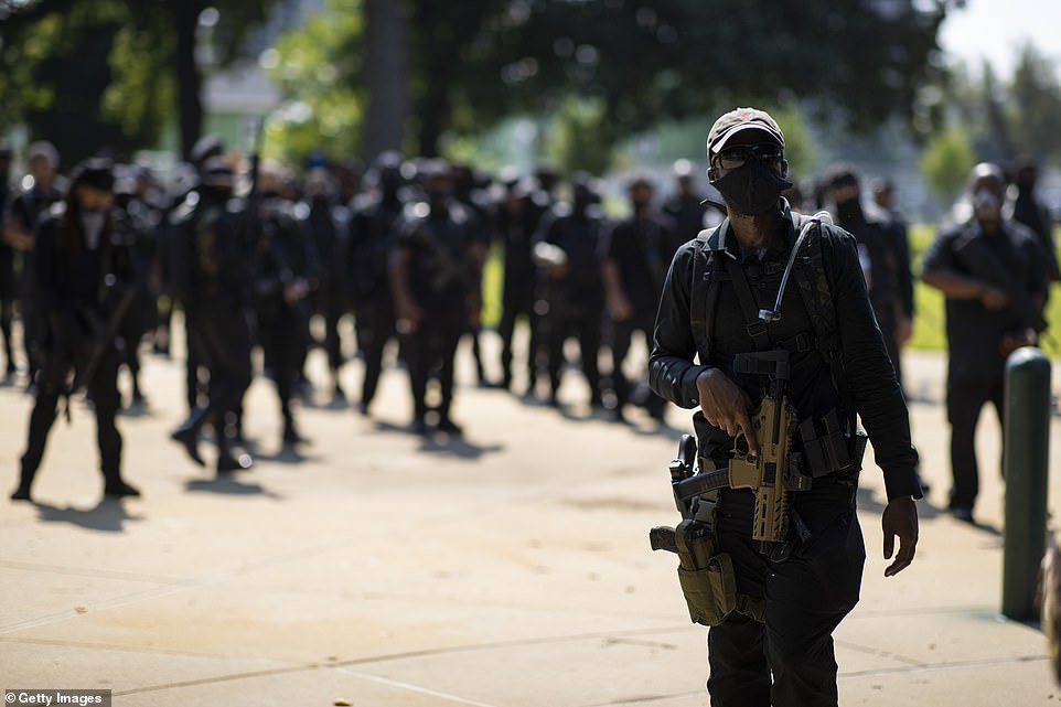NFAC members are seen above carrying firearms during a march in Louisville, Kentucky, on Saturday