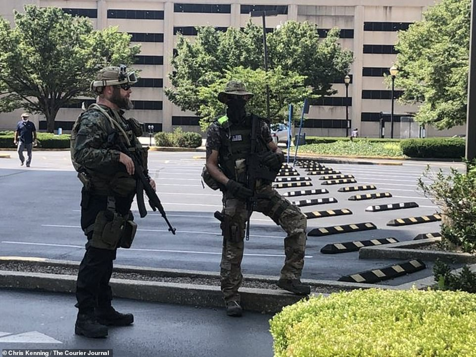 Two members of the Three Percenters militia are seen above in tactical gear near city hall in Louisville, Kentucky, on Saturday