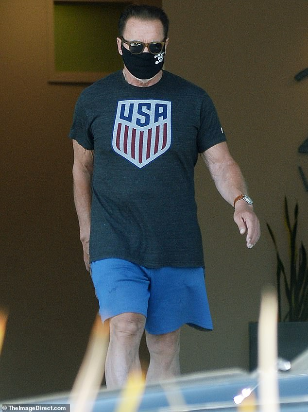 Arnold Schwarzenegger shows off toned arms in patriotic t-shirt as he wears his 'we'll be back' mask