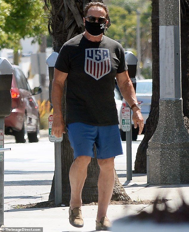 Still a beefcake:The 72-year-old former California Governor showed off his toned arms in a fitted patriotic T-shirt while enjoying a masked stroll
