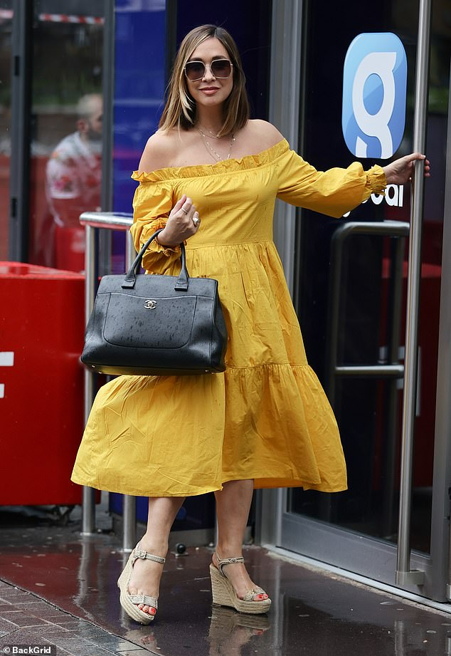 Gorgeous:The mother-of-three teamed the colourful dress with simple nude wedges and a black Chanel handbag