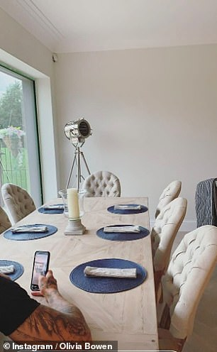 Settling in: Olivia's reality star husband Alex could be seen sitting at their 2.4m dining table and checking his phone