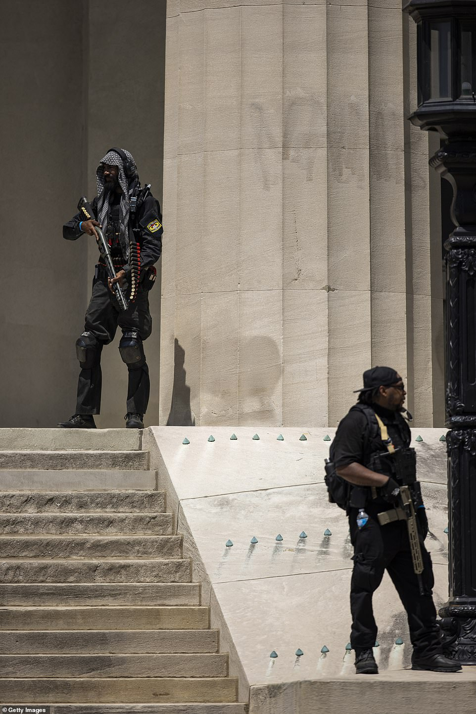 Two members of the armed militia are seen above in Louisville, Kentucky, during a demonstration on Saturday