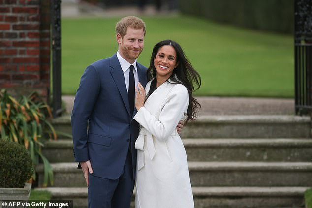 Meghan Markle and Prince Harry pose for a photograph in the Sunken Garden at Kensington Palace in west London on November 27, 2017, after the announcement of their engagement