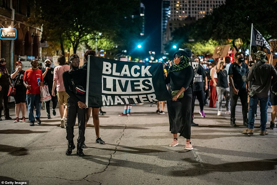 Marchers carry a Back Lives Matter banner through the streets of Austin, Texas, during a march on Sunday night