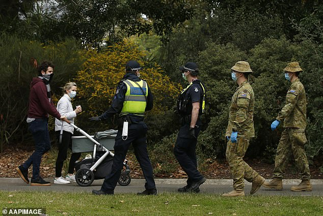 Australian Defence Force personnel and Victoria police officers patrol the Royal Botanic Gardens on Sunday, ensuring everyone wears face masks