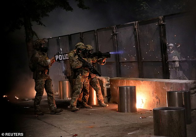Federal law enforcement officials pictured aiming at protesters standing outside a fence they set up around the Justice Center and Federal Courthouse in Portland on Friday