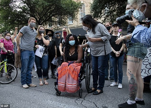 Whitney Mitchell chokes back tears as she takes part in a vigil for her fiance, Garrett Foster, who was shot dead in Austin