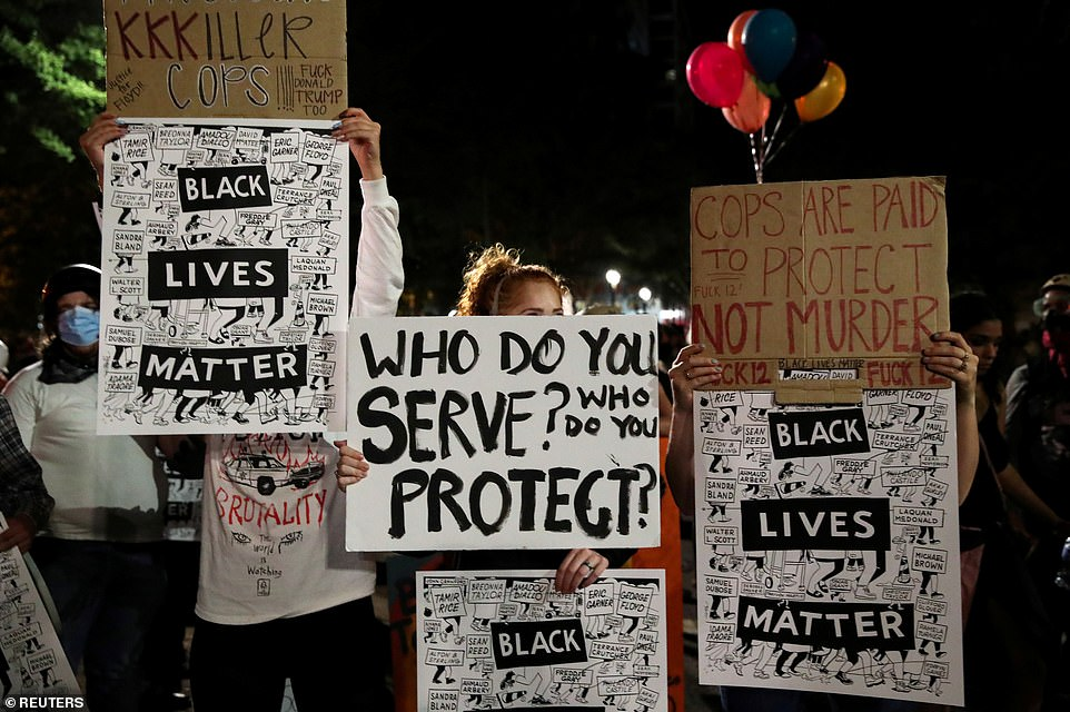 Demonstrators hold placards reading 'Black Lives Matter' and 'Cops are paid to protect not murder' during protests