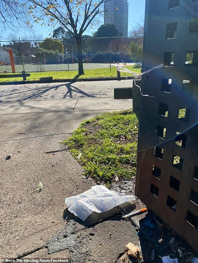 A syringe can be seen next to a bin at a public park in Melbourne frequented by children