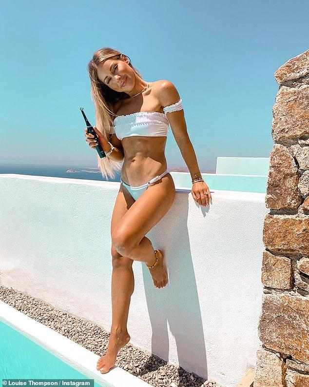 Beach babe:Louise showcased her incredible figure when she slipped into a strapless white ruffle bikini on Wednesday