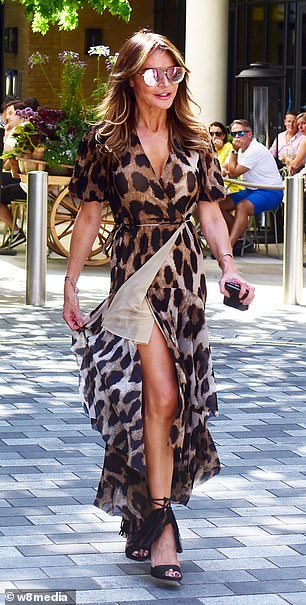 Lizzie Cundy, 52, commands attention in a leopard print maxi dress and tasseled stilettos in Soho
