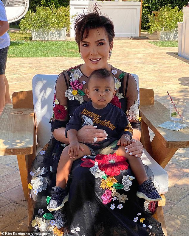 Garden party: Kris, 64, cuddled up to Psalm on one of the property's stylish patio chairs