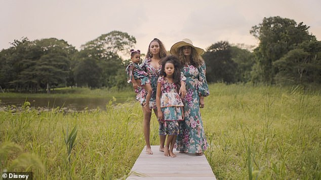 Family time:All four of them are wearing matching floral outfits as they gather together in a meadow as if standing for a portrait