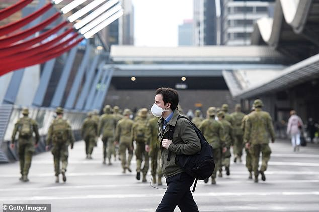Melbourne resident walks past Australian Defense Force personnel as city continues to go through lockdown third stage