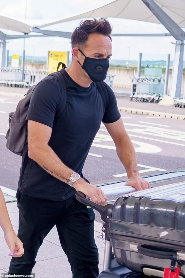 Safety first: In keeping with government guidelines, Ant donned a black face mask as he left their taxi to grab a trolley to push three huge suitcases into the departures terminal
