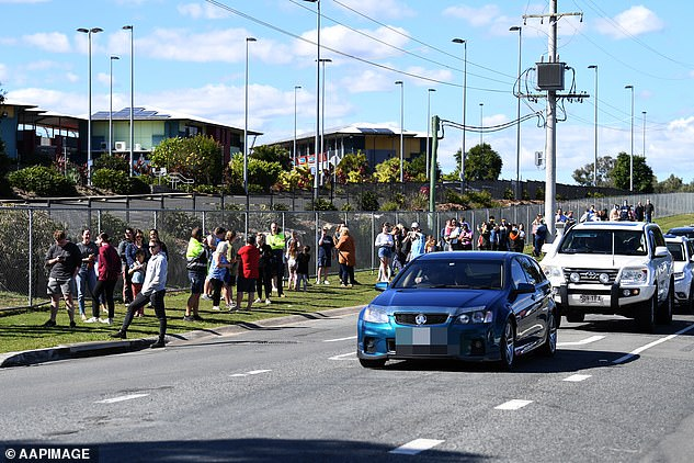 People line up in their cars and on foot to get COVID-19 tested at the Parklands Christian College on Wednesday