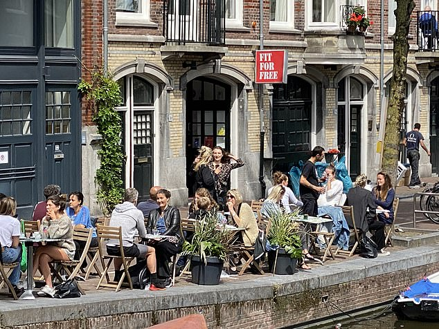 While 120 countries in the world ordered citizens to wear masks in public places to prevent the spread of Covid-19, the Dutch are doing things differently. Pictured, people enjoying a drink in Amsterdam