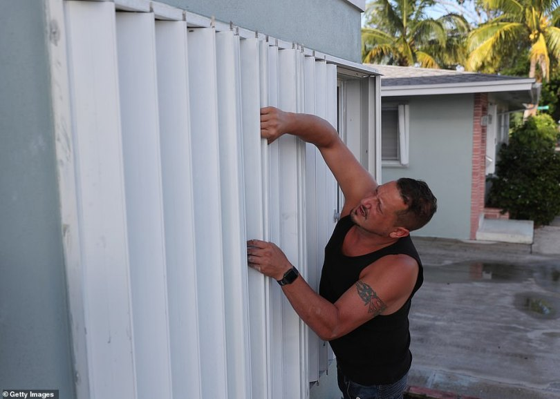 Anthony Perrone pulls the hurricane shutters closed on his home on Friday in Lake Worth, Florida. Perrone said he closed the shutters to prepare his home for the possible arrival of Hurricane Isaias