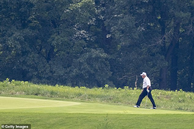 Trump walks on the golf course on Saturday just moments before sharing the video