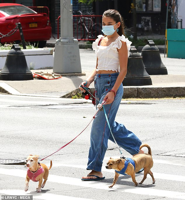 Dog duty: Meanwhile, Katie's 14-year-old daughter Suri, who she shares with actor ex husband Tom Cruise, 58, was busy enjoying a stroll through the city with her and her mom's darling Chihuahua pups