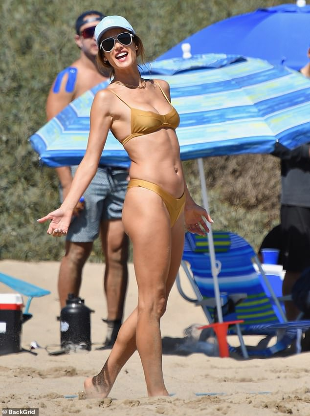 Game time:The 39-year-old Victoria's Secret Angel showed off her svelte physique as she eagerly body surfed and engaged in a competitive game of beach volleyball with pals