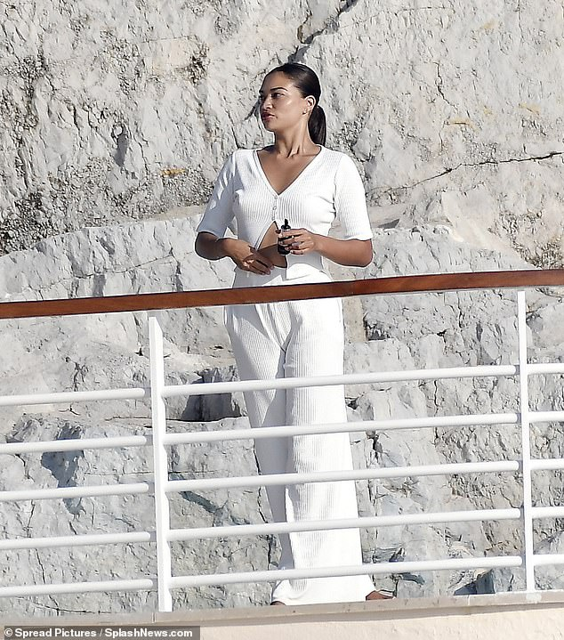 Gorgeous:The Victoria's Secret model, 29, nailed summer chic in white flared trousers which she teamed with a cardigan that flashed her bronzed abs
