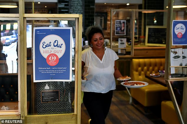 A waitress serves breakfast at Maggie's cafe in London today on the opening day of Eat Out to Help Out scheme