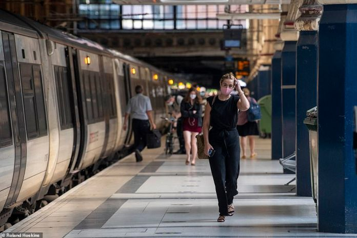 A woman scratches her head as she walks down a gangway from a train as she gets into Liverpool Street Station in central London