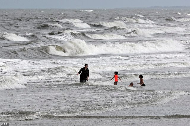 People swim in the ocean as Tropical Storm Isaias approaches in Kure Beach, North Carolina, on Monday