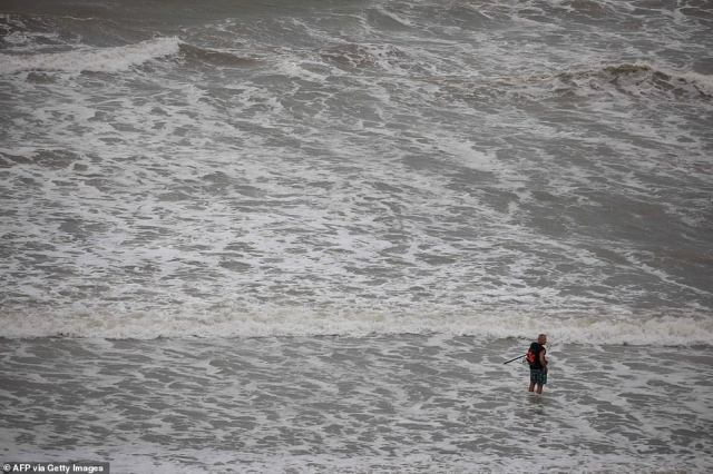 A man continued to fish on the beach in North Myrtle Beach, South Carolina, on Monday as Isaias made its approach toward the coastline