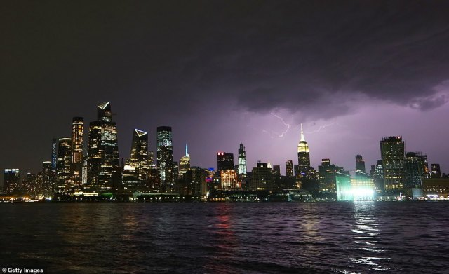 Lightning illuminates the skies above New York City on Monday night as showers and thunderstorms hit the area a day before the arrival of Isaias