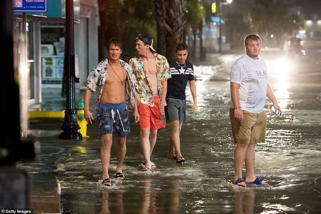 A group of people are seen above walking along a flooded roadway in Myrtle Beach, South Carolina, late on Monday