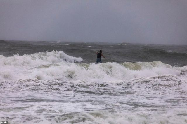 A surfer rides the stormy seas off Garden City, South Carolina, as Hurricane Isaias neared the Carolinas on Monday