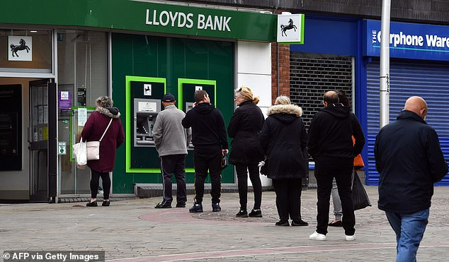 Customers in Barrow-in-Furness forced to wait outside a Lloyds branch in May 2020. Britain's largest bank said it would open its doors for longer following the easing of lockdown
