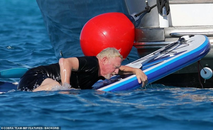Easy goes it! Boris was seen hauling himself back on his paddle board in the water