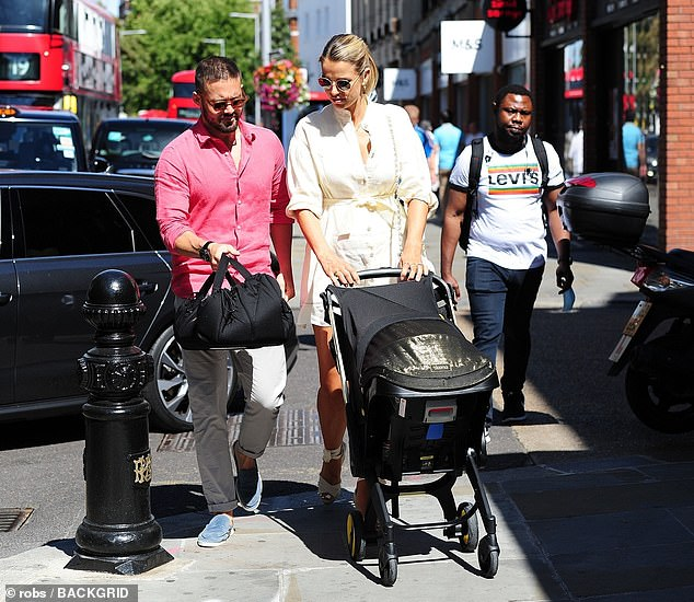 Happy family: Vogue and Spencer doted on their baby daughter as they wheeled the pram into the Town Hall
