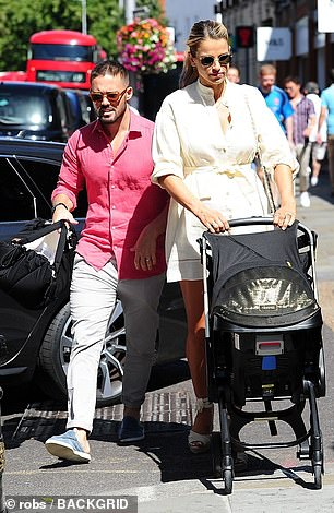 Lovely: She opted for a thigh-skimming shirt dress as she wheeled the pram into the Town Hall